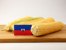 Haiti flag on a wooden panel with corn isolated on a white backg. Round royalty free stock photos