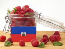 Haiti flag on a wooden panel with raspberries isolated on a whit. E background royalty free stock image
