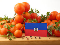 Haiti flag on a wooden panel with tomatoes isolated on a white b. Ackground royalty free stock photography