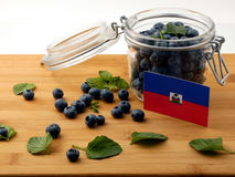 Haiti flag on a wooden plank with blueberries on white. Haiti flag on a wooden plank with blueberries stock photo