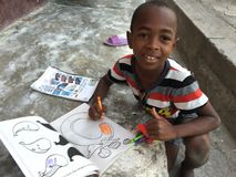 Haitian boy coloring. Young boy from Haiti drawing in book Royalty Free Stock Photos