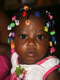 Haitian infant adorned with colorful barrettes in rural Haiti. Stock Photo