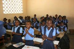 Haitianische Schulkinder begrüßen Besucher in ihrem Klassenzimmer Stockfotografie