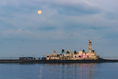 Haji Ali Mosque with Moonset. Haji Ali Mosque in Mumbai, India waking up to full moon set and pink light still to be switched off to welcome Sun Stock Photography
