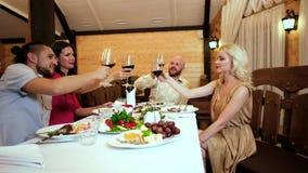 Haka-hakan lyckliga vänner som möts i kafét, familjferie, lyckligt folk i restaurang, klirrar exponeringsglas med vin som talar arkivfilmer