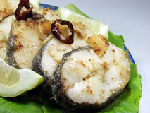 Hake. Slices of fried hake whit garlic and lemon royalty free stock images