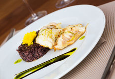 Hake with black rice and sauce Stock Photos