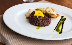 Hake with black rice and sauce Royalty Free Stock Photography