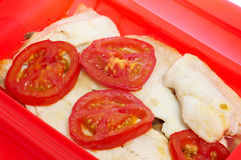 Hake en papillote. Some slices of hake cooked en papillote with slices of tomato and other vegetables royalty free stock images