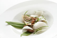 Hake fillet. With black radish and brown beans Stock Image