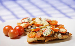 Hake fish with tomatoes. A picture of freshly baked hake fish with mushrooms, tomatoes and blue cheese Royalty Free Stock Image