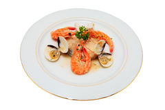 Hake in sauce. Spanish hake with prawns and clams in green sauce trimmed and isolated Royalty Free Stock Photography