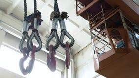 Haken, die am Fabrikstrahlnkran in der Anlage hängen Arbeit in einem Lager des Metalls, Transport von Produkten Abschluss oben stock video footage
