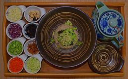 Hakka Tea Rice (Lei Cha) served on wooden tray. Ready to be consumed. The ingredients served on separate small saucers on the side include cashew nuts, cabbage royalty free stock photo
