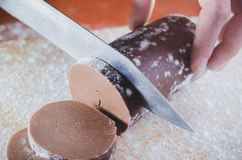 Hakkend chocoladedeeg voor gebakjes met een mes op een houten die raad met tarwemeel wordt bestrooid stock foto