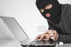 Hakker in balaclava die een kaart in linker houden en iets met rechts op laptop toetsenbord typen royalty-vrije stock afbeeldingen