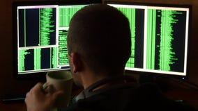 Hakker brekende code en het drinken van de kop bij uw bureau Het misdadige systeem van het hakker doordringende netwerk van zijn  stock videobeelden