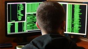 Hakker brekende code en het drinken van de kop bij uw bureau Het misdadige systeem van het hakker doordringende netwerk van zijn  stock footage