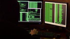 Hakker brekende code Misdadige hakker met het zwarte systeem van het kap doordringende netwerk van zijn donkere hakkerruimte stock videobeelden