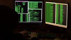 Hakker brekende code Misdadige hakker met zwarte kap stock footage