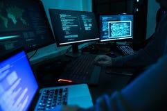 Hakker die aan computer cyber misdaad werken stock fotografie