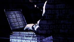 Hakker die aan zijn laptop werken stock footage