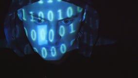 Hakker die met een kap aan een computer, binaire code werken die op zijn gezicht ontwerpen Brondiecode over een boze vijandige me stock video