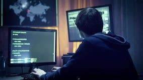 Hakker in jasje die met een kap computer met behulp van bij lijst stock footage