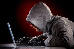 Hakker met laptop stock foto's