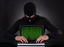 Hakker stealing gegevens van een laptop computer Stock Foto's