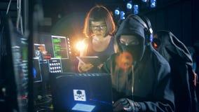 Hakkers die met apparaten werken terwijl het barstende systeem, omhoog sluit stock videobeelden