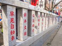 HAKONE, ЯПОНИЯ - 2-ОЕ ИЮЛЯ 2017: Письма Japanesse в информативном совете, с вишневыми цветами красивого вида позади Стоковое Изображение