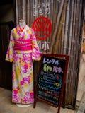 HAKONE JAPAN - JULI 02, 2017: Den härliga och färgrika kimonot med blommor skrivar ut, med informativa bokstäver för en japanesse Arkivbild