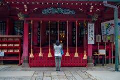HAKONE, JAPAN - 2. JULI 2017: Nicht identifizierte Frau stoppt, um am Hakone-Schreintempel in Hakone, Japan zu beten Lizenzfreie Stockfotos