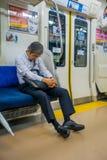 HAKONE JAPAN - JULI 02, 2017: Oidentifierad man som sover på inre av drevet under regnig och molnig dag Arkivbilder