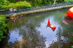 HAKONE JAPAN - JULI 02, 2017: Oidentifierat folk som ser röd abstrakt installation i dammet av Hakone öppen luft Royaltyfria Foton