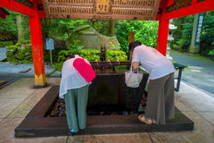 HAKONE JAPAN - JULI 02, 2017: Oidentifierat folkdricksvatten på skriva in av röda Tori Gate på den Fushimi Inari relikskrin Royaltyfria Bilder