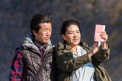 HAKONE JAPAN - NOVEMBER 5, 2017: Det japanska paret gör selfies utomhus skjutit selektivt för fokus royaltyfri bild