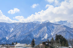 Hakuba mountain range  and  Hakuba village houses  in the winter. With snow on the mountain and blue sky and clouds background in Hakuba  Nagano Japan Stock Photo