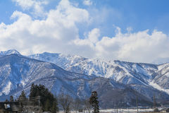 Hakuba mountain range  and  Hakuba village houses  in the winter. With snow on the mountain and blue sky and clouds background in Hakuba  Nagano Japan Stock Photos