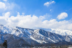 Hakuba mountain range   in the winter with snow on the mountain. And blue sky and clouds background in Hakuba  Nagano Japan Royalty Free Stock Image