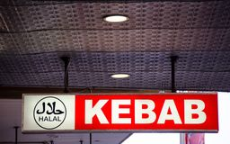 Halal Logo on Red Kebab restaurant sign. A Halal Logo on Red Kebab restaurant sign. also spelled hallal or halaal, refers to what is permissible or lawful in Royalty Free Stock Photo