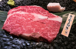 Halal wagyu beef steak on plate. Halal raw wagyu beef steak, sliced into cutlets, served on plate. The paper is a tag to indicate it`s 100% halal authenticity Stock Image