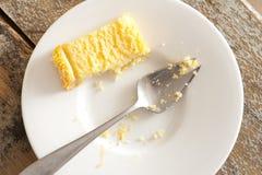 Halb aufgegessene Scheibe des Kuchens auf einer Platte Lizenzfreies Stockfoto