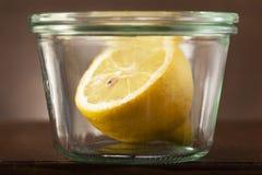 Halb eine Zitrone in einem Weinlesekleinen Glastopf lizenzfreies stockfoto