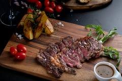Halb gare Fleischrippenaugen-Steakscheiben in der Wanne auf dem Hacken hölzern lizenzfreie stockfotos