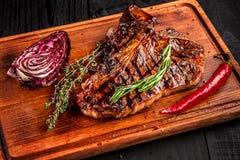 Halb gares gegrilltes Steak auf rustikalem Schneidebrett mit Rosmarin und Gewürzen, dunkler rustikaler hölzerner Hintergrund, Dra Stockfoto