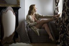 Halb gekleidete Frau, die zu Hause durch Fenster sitzt stockfoto