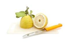 Halb japanische Zitrone auf Schneidebrett mit dem Messer, getrennt Stockfotos