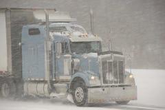 Halb-LKW, der in einen Blizzard antreibt stockfotografie